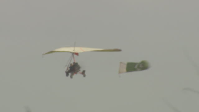 ultralight aircraft in flight, flying w/ pakistani banner attached to rear, tree into fg. aviation, ultralighting, sport. - peshawar stock videos & royalty-free footage