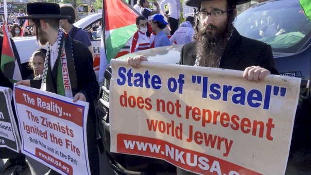 ultra-orthodox jewish men hold anti-zionism placard signs in opposition to the jewish state of israel as people participate in a pro-palestinian... - judaism stock videos & royalty-free footage