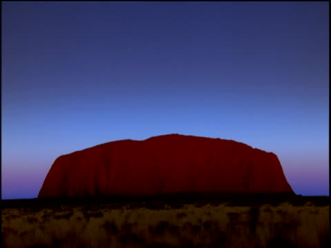 uluru against bright blue sky fades to black as night falls - エアーズロック点の映像素材/bロール