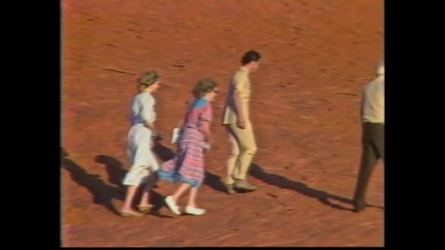 vídeos y material grabado en eventos de stock de prince charles and princess diana out of mini bus / meeting aboriginal elders / press / uluru zoom in the charles and diana walking on lower slopes /... - 1983