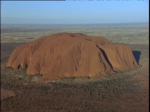 uluru blue sky in background dusty bush in foreground - エアーズロック点の映像素材/bロール