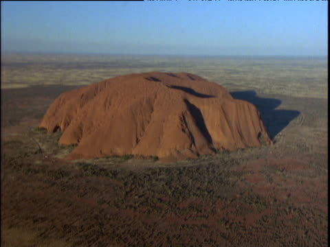 uluru blue sky in background red dusty bush in foreground - エアーズロック点の映像素材/bロール