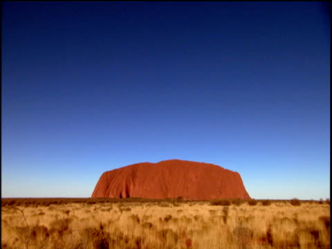 uluru in distance under blue sky grassland surrounding rock australia - エアーズロック点の映像素材/bロール