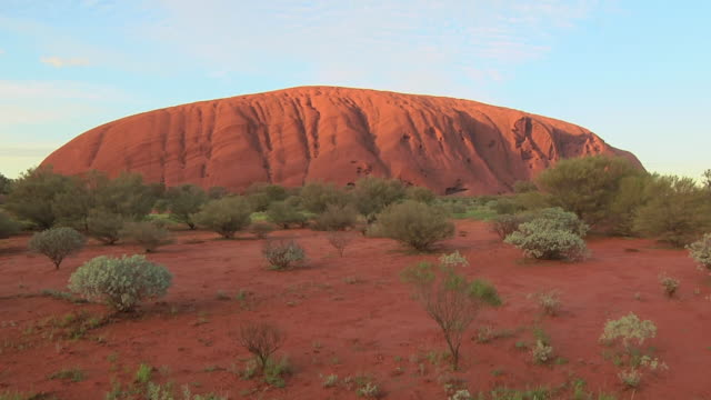 ms uluru rock formation with shrub in foreground / alice springs, northern territory, australia - red rocks stock videos and b-roll footage