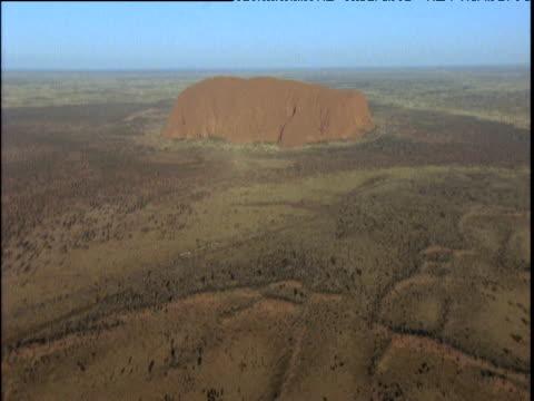 Uluru surrounded by brown bush Australia