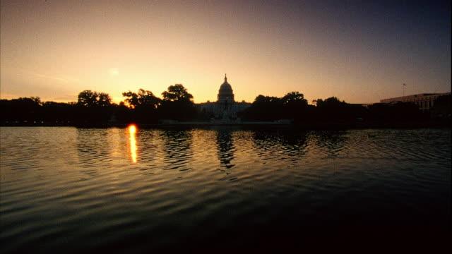 vídeos y material grabado en eventos de stock de xws ulysses s grant memorial pool w/ rippling water ducks swimming fg trees capitol building silhouette bg - ulysses s grant