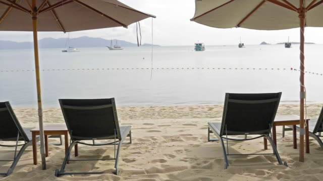 umbrella and chair on the beach - sun lounger stock videos & royalty-free footage