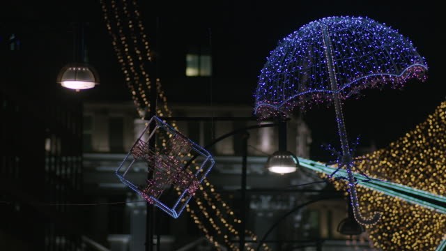 Umbrella and present-shaped lights hang in the Oxford Street Christmas light display of 2011, London, UK.