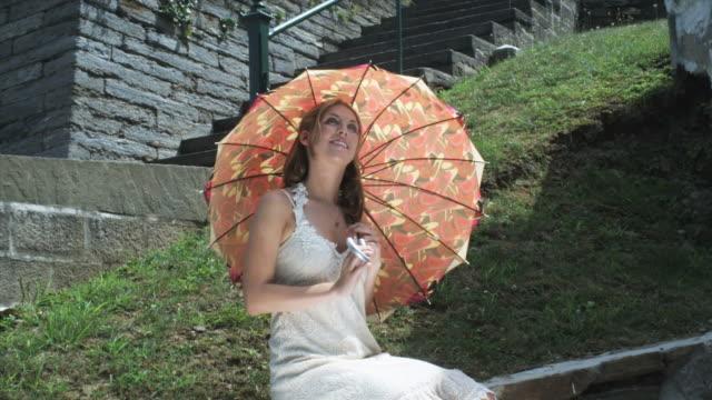 hd crane: umbrella angel sitting on the ledge - ledge stock videos & royalty-free footage