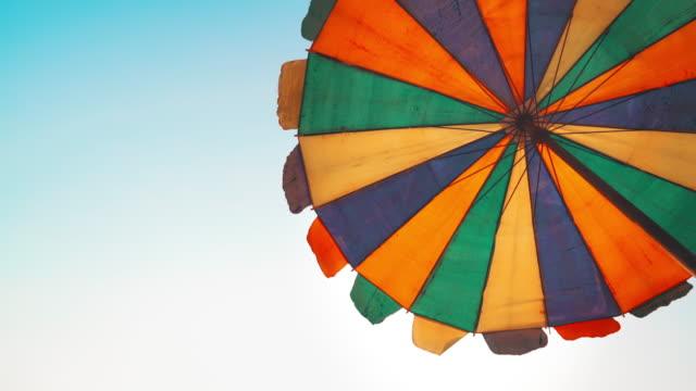 stockvideo's en b-roll-footage met paraplu op zandstrand met blauwe hemelachtergrond - zonnescherm gefabriceerd object