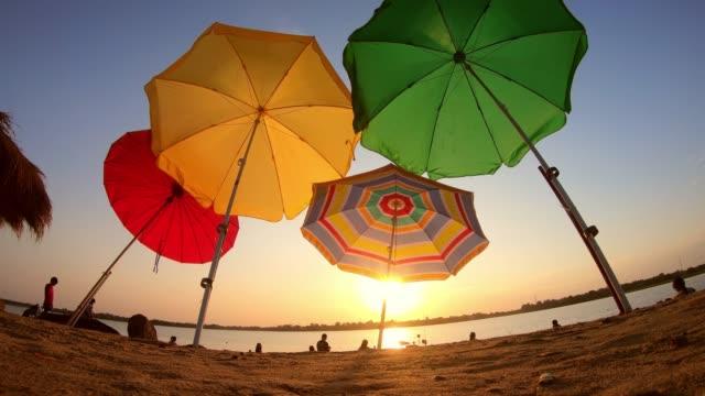 umbrella on tropical sunset beach time lapse - beach umbrella stock videos and b-roll footage