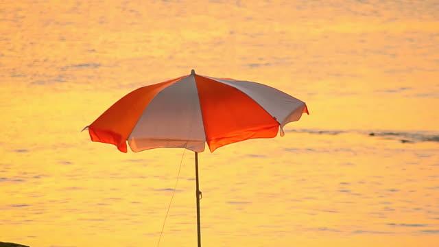 Umbrella on tropical sunset beach