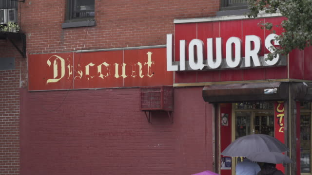 umbrella tops cross the frame underneath a nondescript discount liquor store sign as it rains in brooklyn. - store sign stock videos & royalty-free footage