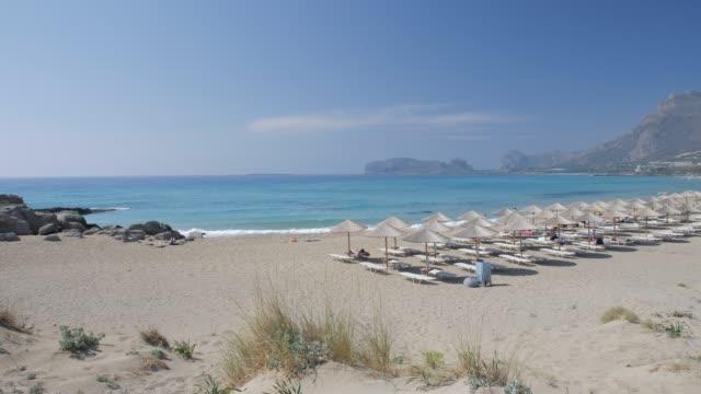 umbrellas on the beach and emerald seas at falassarna beach in western crete, greek islands, greece, europe - grekisk kultur bildbanksvideor och videomaterial från bakom kulisserna