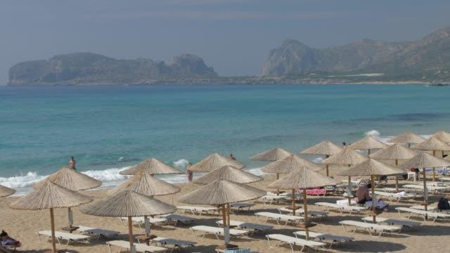 umbrellas on the beach and emerald seas at falassarna beach in western crete, greek islands, greece, europe - sunbed stock videos & royalty-free footage