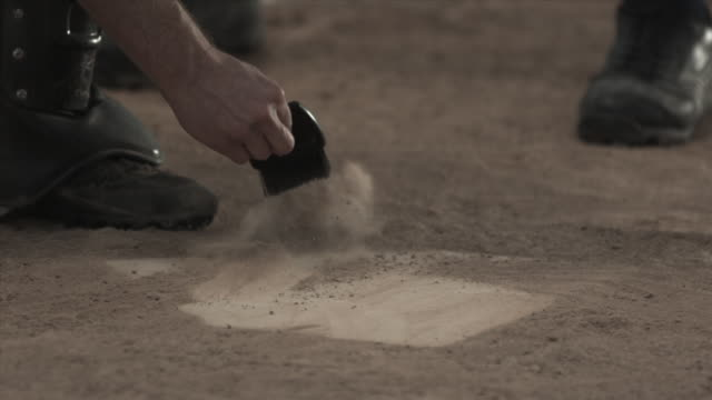 SLO MO CU Umpire dusting home plate on baseball field / Lancaster, California, USA