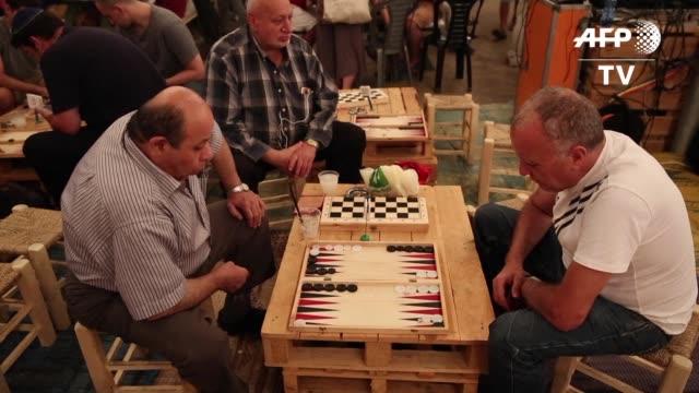 vídeos y material grabado en eventos de stock de un centenar de israelies y palestinos dejan a un lado sus diferencias para enfrentarse en las tablas reales un juego de mesa muy extendido en medio... - de lado a lado