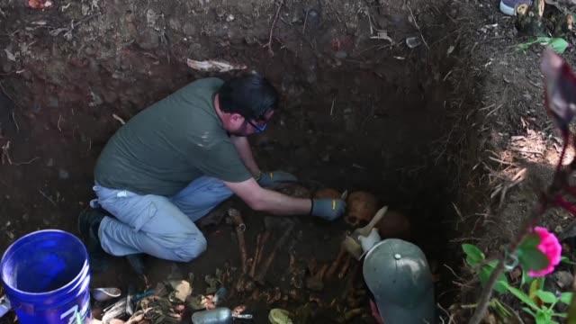 un equipo forense desenterraba el miercoles parte de las osamentas de 11 victimas de la masacre de el mozote cometida por el ejercito durante la... - guerra civil stock videos and b-roll footage