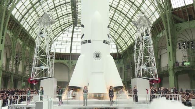 Un escenario inspirado en el espacio trabajadores en trajes espaciales y el lanzamiento de un cohete para cerrar el desfile la coleccion...