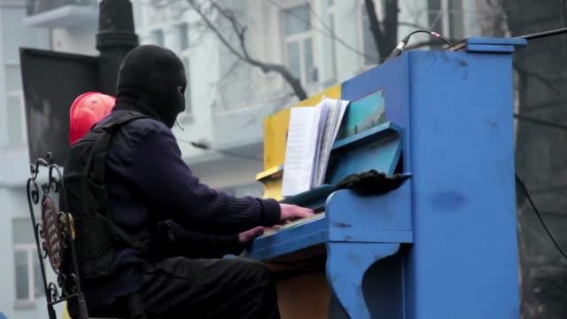 vídeos de stock, filmes e b-roll de un insolito concierto de piano fue llevado a cabo este lunes por varios protestantes de ucrania en una de las barricadas erigidas en el centro de... - barricada divisa