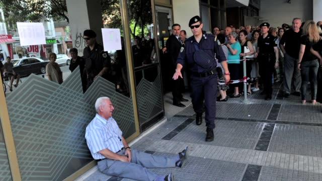 un jubilado griego se sume en un mar de lagrimas delante de un banco al no poder soportar ver a su pais en esta miseria - delante de stock videos and b-roll footage