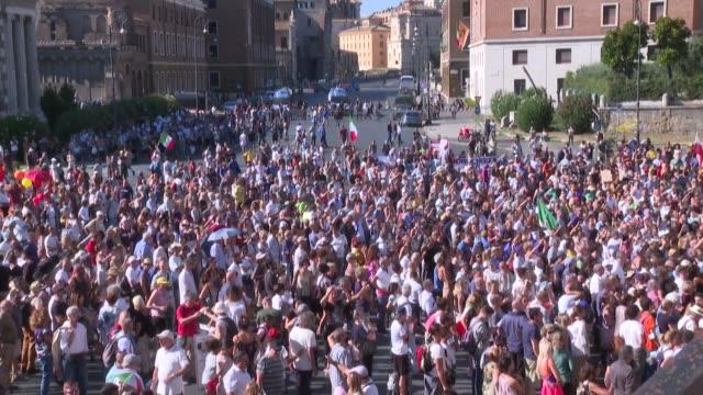vídeos y material grabado en eventos de stock de un millar de personas se manifestaron el sábado en el centro de roma para protestar contra la obligación de vacunar a los niños en edad escolar o de... - llevar