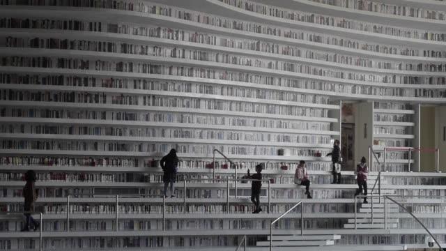 una biblioteca futurista china asombro a los amantes de los libros alrededor del mundo con una arquitectura de estantes ondulados de piso a techo - biblioteca stock videos and b-roll footage