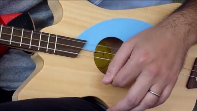 vídeos y material grabado en eventos de stock de una guitarra de tres cuerdas para ninos creada por un uruguayo producida en china y distribuida desde estados unidos se volvio global gracias a... - instrumento de cuerdas