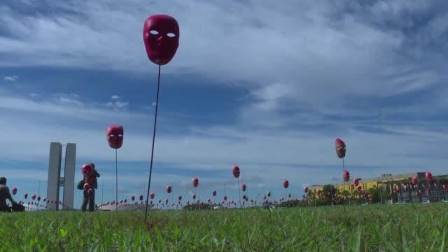 una instalacion artistica de 500 mascaras rojas frente al congreso de brasil en la explanada de los ministerios en brasilia busca evidenciar la... - acanthaceae stock videos & royalty-free footage