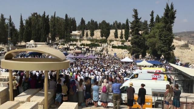 una multitud de israelies despidio este viernes a la pareja de colonos asesinada frente a sus cuatro hijos en la cisjordania ocupada - multitud stock videos & royalty-free footage
