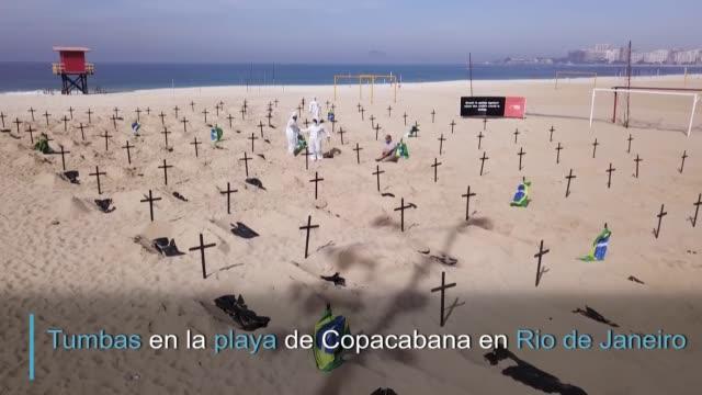 vídeos y material grabado en eventos de stock de una ong cavó tumbas simbólicas en la playa de copacabana en rio de janeiro en homenaje a los miles de muertos por covid-19 en brasil y para denunciar... - postura