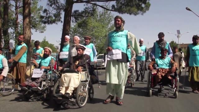 vídeos de stock e filmes b-roll de una veintena de afganos mutilados por la guerra comenzaron el martes a recorrer cientos de kilometros hasta la capital para exigir la paz entre el... - exigir