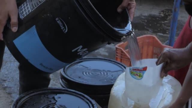 unas 200 personas hacen fila en una calle de caracas para recolectar agua de un viejo hidrante - agua stock videos & royalty-free footage