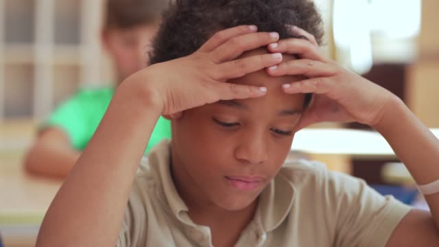uncertain elementary schoolboy looking at the exam in school while holding on to his head - schoolboy stock videos & royalty-free footage