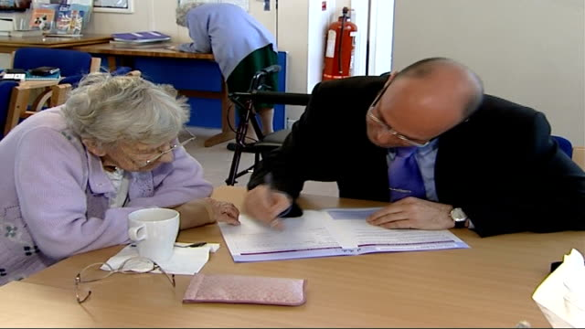 unclaimed benefits by elderly paddy helping elderly lady fill out form reporter to camera - 麦わら帽子点の映像素材/bロール