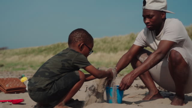 uncle and nephew building a sand castle