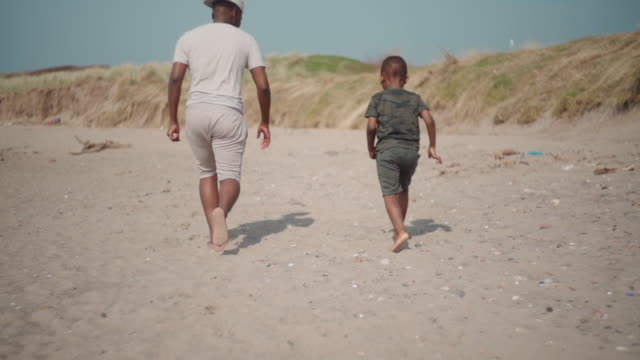uncle and nephew running together on the beach