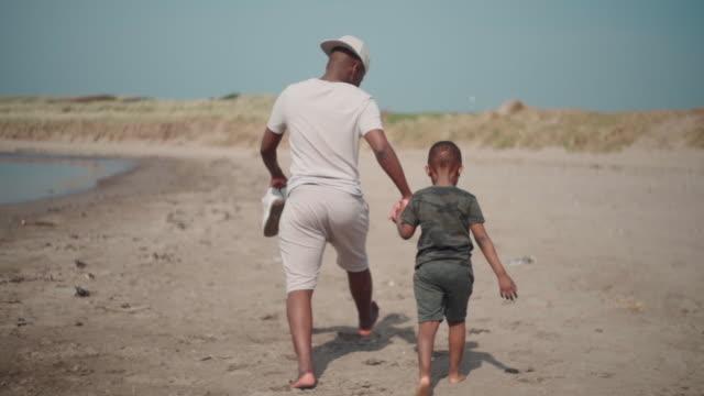 uncle and nephew walking along the beach - 甥点の映像素材/bロール
