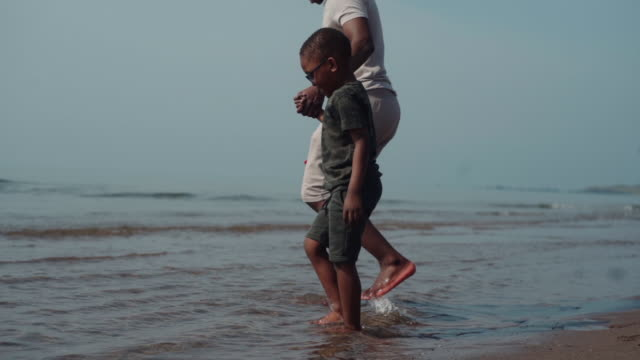 uncle and nephew walking into the water together