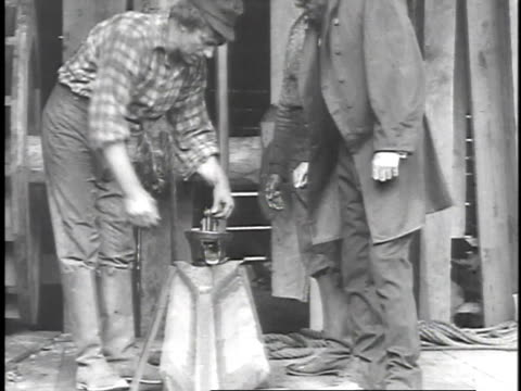1923 reenactment uncle billy smith and colonel edwin drake inspecting the oil coming out off the drill / united states  - 1923 stock-videos und b-roll-filmmaterial