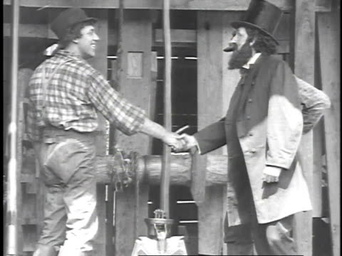 1923 reenactment uncle billy smith drilling oil as colonel edwin drake arrives to inspect his work / united states  - 1923 stock-videos und b-roll-filmmaterial