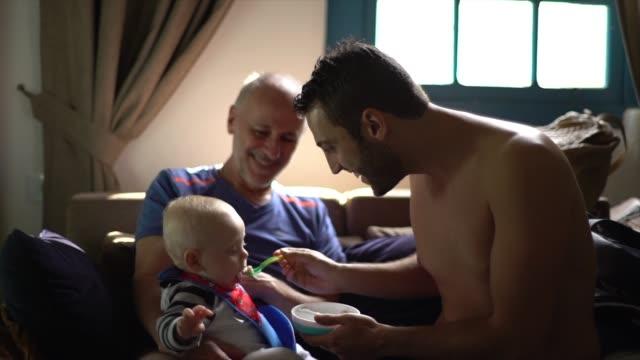 vídeos de stock, filmes e b-roll de tio que alimenta um bebé em um vestiário - comida de bebê