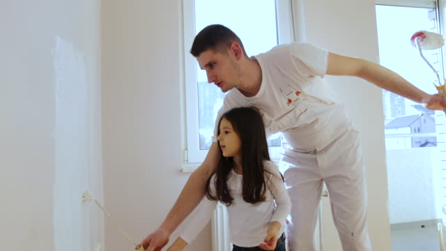 uncle teaching cute little girl how to paint a room - renovation stock videos & royalty-free footage