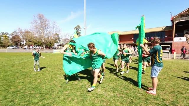 pan under 175 grand final navarre grasshoppers v carisbrook redbacks navarre run through the banner prior to the match during the maryborough... - バナー看板点の映像素材/bロール