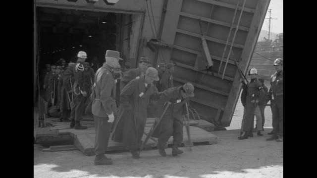under armed guard wounded communist chinese prisoners of war leave the uss russell county and limping to a waiting bus // africanamerican war wife... - new york daily news stock videos and b-roll footage