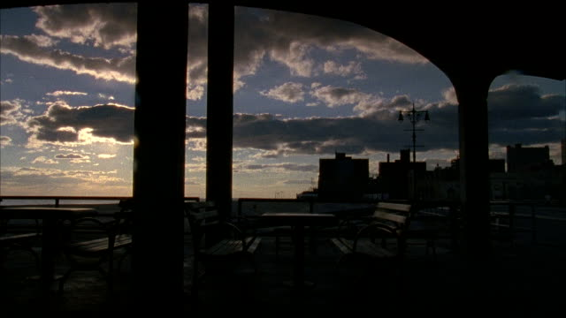 sunset under deserted open air pavilion w/ empty park benches tables sun setting distant bg apartment buildings in silhouette along skyline no people... - coney island brooklyn stock videos & royalty-free footage