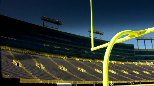 Under goal posts FG empty seating glass windows of suites stadium lights BG blue sky Iconic dramatic Old City Stadium Green Bay Packers NFL football...