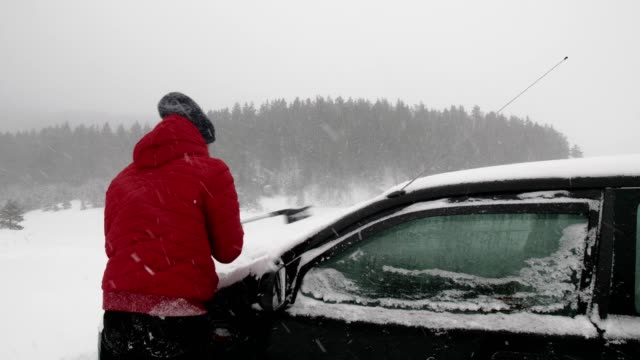 under the snow. car pov, driving on snow covered road, first snow falling. active senior man scooping the snow from the car. - snowplough stock videos & royalty-free footage
