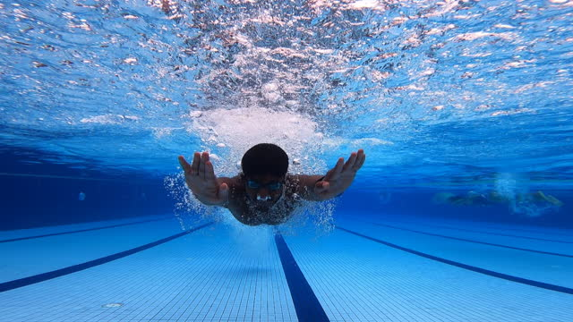 under water asian indian sportperson swimming butterfly style - sportsperson stock videos & royalty-free footage