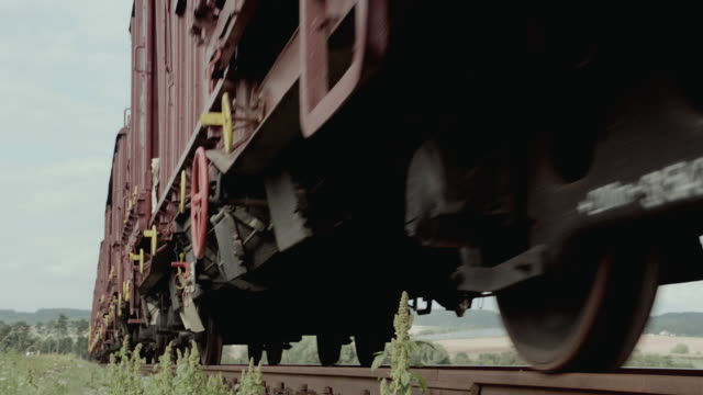 vídeos de stock e filmes b-roll de cu undercarriage of freight train with red and black cars traveling down a track in the countryside - chassi